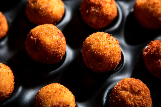 High angle of tasty roasted cheese balls in baking dish on concrete table in the kitchen