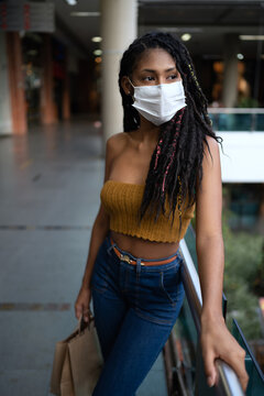 Portrait of attractive young afro latin woman wearing a facemask and holding shopping bags in commercial mall, Colombia