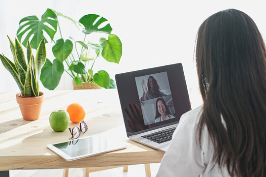 Stock photo of asian doctor greeting her patient in video-conference.