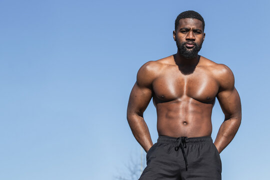 Shirtless muscular black male athlete standing hands on hips resting during workout in sunlight looking at camera