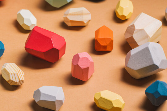 From above of full frame background of assorted wooden blocks in shape of gems scattered on beige table