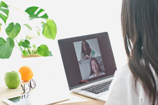 Stock photo of asian doctor talking with her patient via video-call.