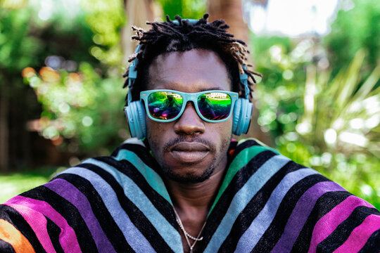 African American male in sunglasses wrapped in colorful towel sitting on meadow in summer park and looking at camera