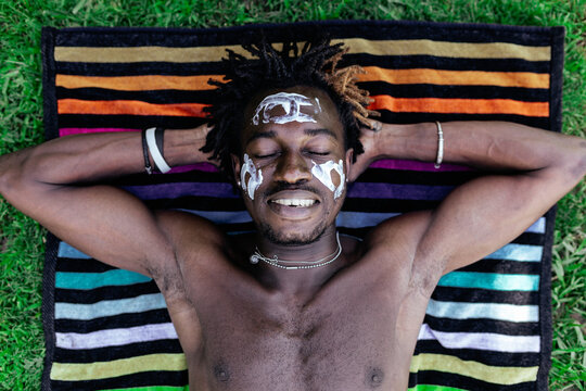Top view of content African American male with naked torso and cream on face lying on towel on meadow and enjoying summer