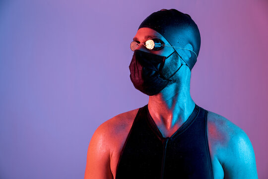 Portrait of a swimmer with mask, cap and goggles looking up