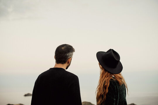Back view of calm unrecognizable couple in stylish clothes and hat standing at mountain seaside landscape on background of blue sea