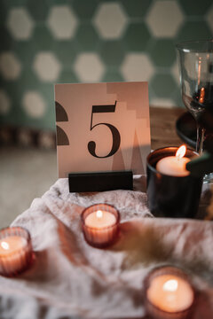 Decoration with number and similar flaming candles near wine glass on crumpled fabric during festive event