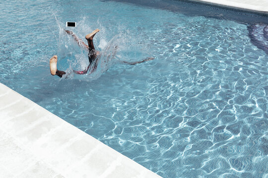 Anonymous African American male falling into swimming pool with smartphone and splashing water