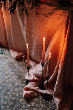 From above of burning wax candles on candlesticks against creased fabric on ornamental tiled floor in building