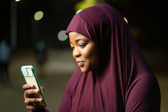 image of traditional  african woman with a smart phone- local muslim lady surfing on social media- outdoor communication concept