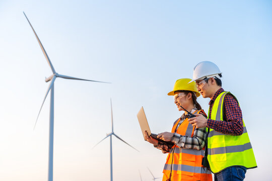 engineer team working with laptop computer against wind turbine farm