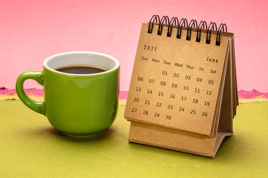 June 2021 - spiral desktop calendar against abstract paper landscape with a cup of coffee, time and business concept