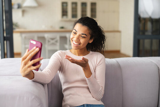 Smiling young mixed-race teenage girl sitting on couch in the living room, video-calling via mobile phone, talking to friend, family, taking selfie for social media, staying connected during pandemic
