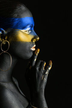 Young Ukrainian woman with blue and yellow paint on her body against dark background