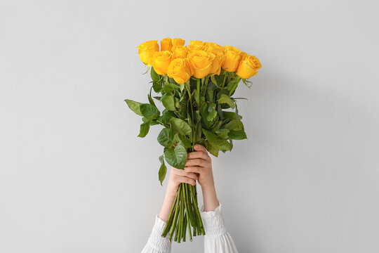 Female hands with beautiful yellow roses on light background