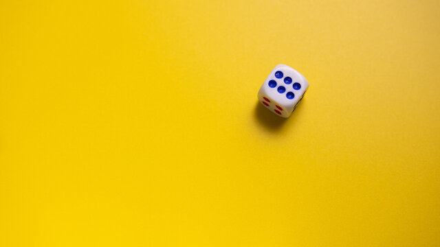 White dice with round dots number six on yellow background close-up. Concept of gambling and chance