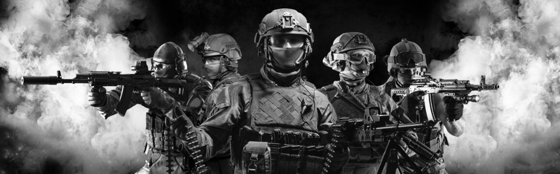 Portrait of five military men. A group of soldiers on a background of smoke. The concept of military operations, special operations, paintball.