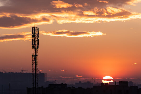 A beautiful sunset over the city, where you can see the 5G high mobile communication tower.