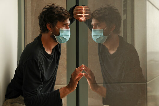 Sad man in isolation due to coronavirus world pandemic. Male in hotel quarantine wearing protective face mask to prevent spreading infectious covid 19 disease. Mirror reflection in window.