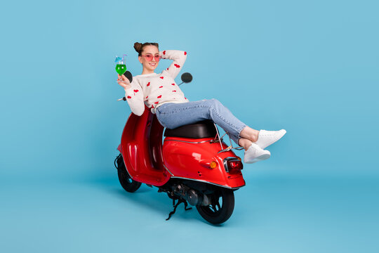 Full size photo of young happy positive girl in glasses relaxing on scooter with cocktail in hand isolated on blue color background