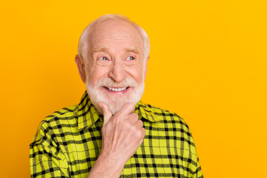 Photo of cheerful old man happy positive smile hand touch chin think look empty space isolated over yellow color background