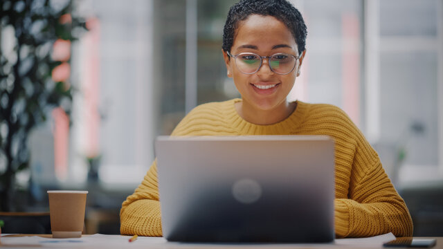 Portrait of Young Latin Marketing Specialist in Glasses Working on Laptop Computer in Busy Creative Office Environment. Beautiful Diverse Multiethnic Female Project Manager is Browsing Internet.
