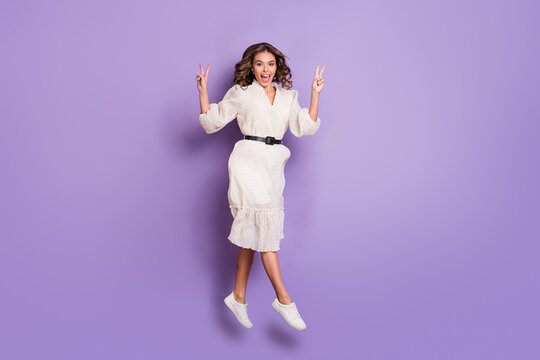 Full length body size photo of woman jumping stepping forward showing v-sign isolated on vivid purple color background