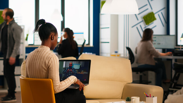 Black woman discussing with remote disabled colleague using video call holding laptop sitting on couch in business modern office. Diverse coworkers planning new financial project in modern company