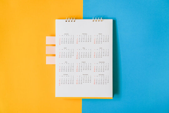 top view of white yearly calendar with small pink tag on grunge yellow and blue paper background