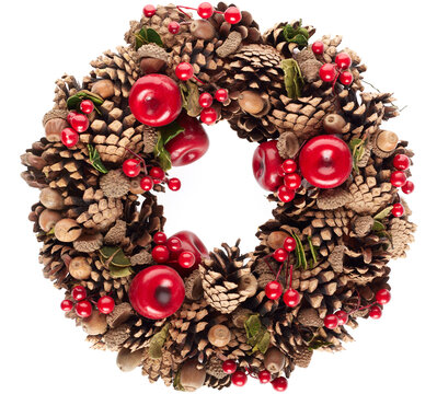 Christmas wreath with pine cones, red berries and acorns isolated on white background