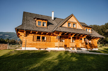 Obraz Wooden cottage in nature in sunny day. Recreation center in the mountains. Modern eko hausing in nature. - fototapety do salonu