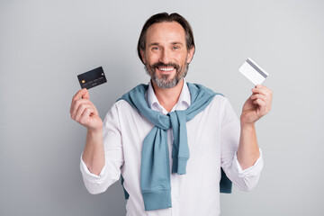 Photo portrait of smiling businessman in white shirt showing plastic bank credit cards isolated pastel grey color background