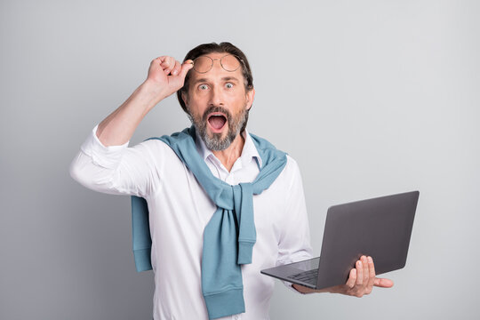 Photo portrait of amazed man holding laptop wearing formal shirt staring opened mouth isolated pastel grey color background