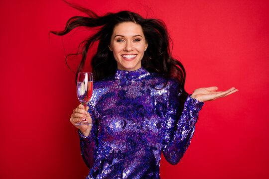 Photo of cheerful happy young woman celebrate party hold champagne glass isolated on red color background