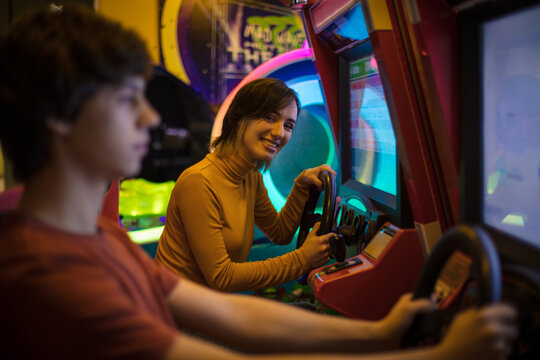 Couple having fun in playroom. Playing a games. Focus is on smiling woman.