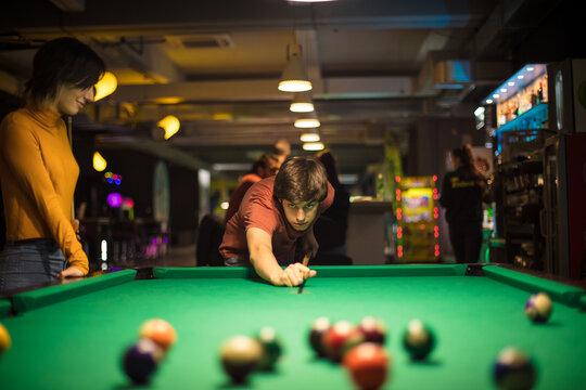 Couple in billiard room. Man playing billiard.