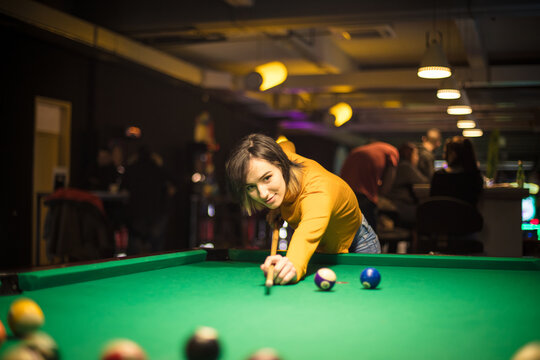 Woman playing billiard alone. Focus is on woman.