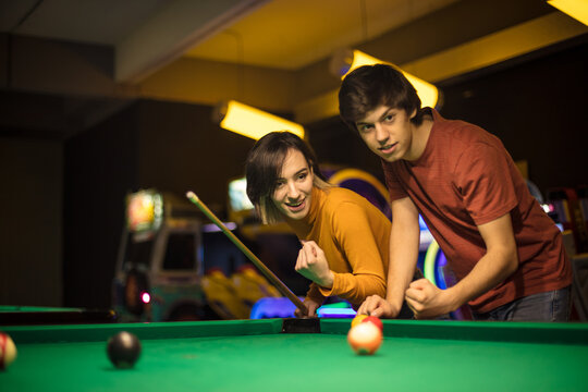 Young couple spending time in billiard room. Woman is a winner.