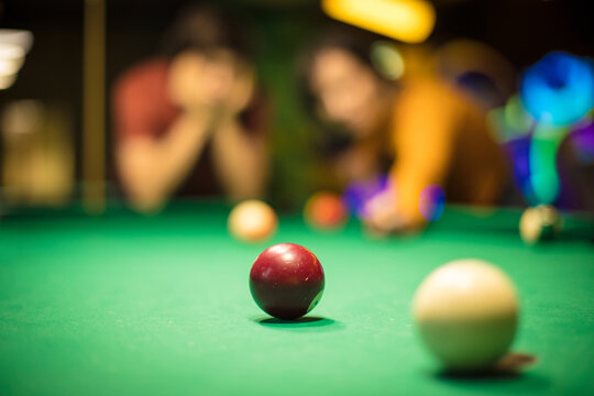 Couple playing a billiard. Focus is on billiards ball.