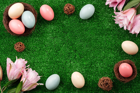 Colorful Easter eggs in the nest on a lawn with pink Double Lily flower.