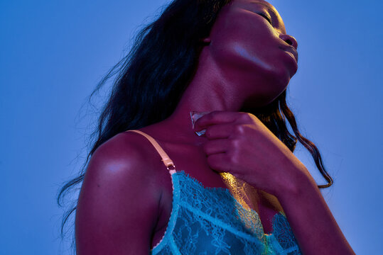 Alluring african american young woman in lace bra looking provocative, touching her skin with melting ice cube while posing in uv light