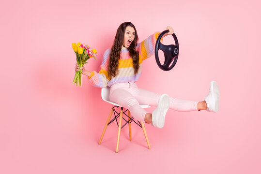 Portrait of beautiful worried funny girl holding in hands tulips driving invisible car hurry rush isolated over pink pastel color background