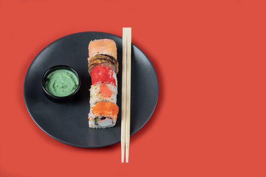 Mixed sushi rolls in a black platter with chopsticks and sauces