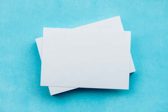 White blank cards in a stack on a blue background. A gentle romantic blank for a postcard.