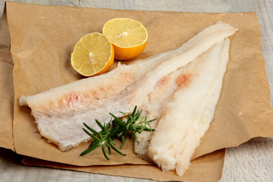 Two Piece of sea fish filet on a paper , decorated with lemon and rosemary, white raw fish filet without a skin