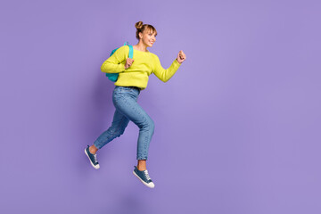 Wall Mural - Full size profile photo of optimistic blond girl jump run wear green sweater jeans isolated on lilac color background