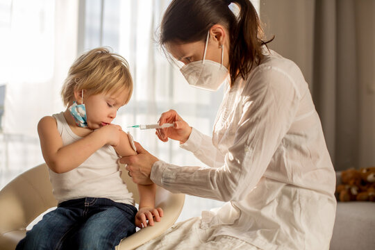 Little toddler boy, getting injection in consulting room from pediatrition