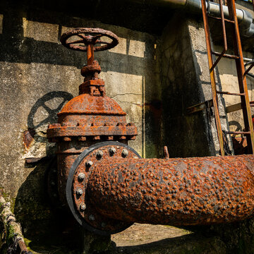 Old rusty water pipe and big valve