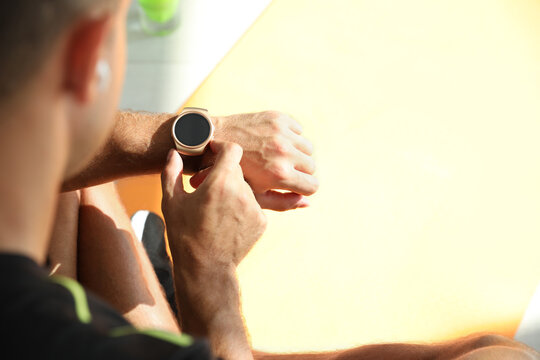 Man checking fitness tracker in gym, closeup. Space for text