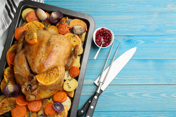 Delicious chicken with oranges and vegetables on light blue wooden table, flat lay